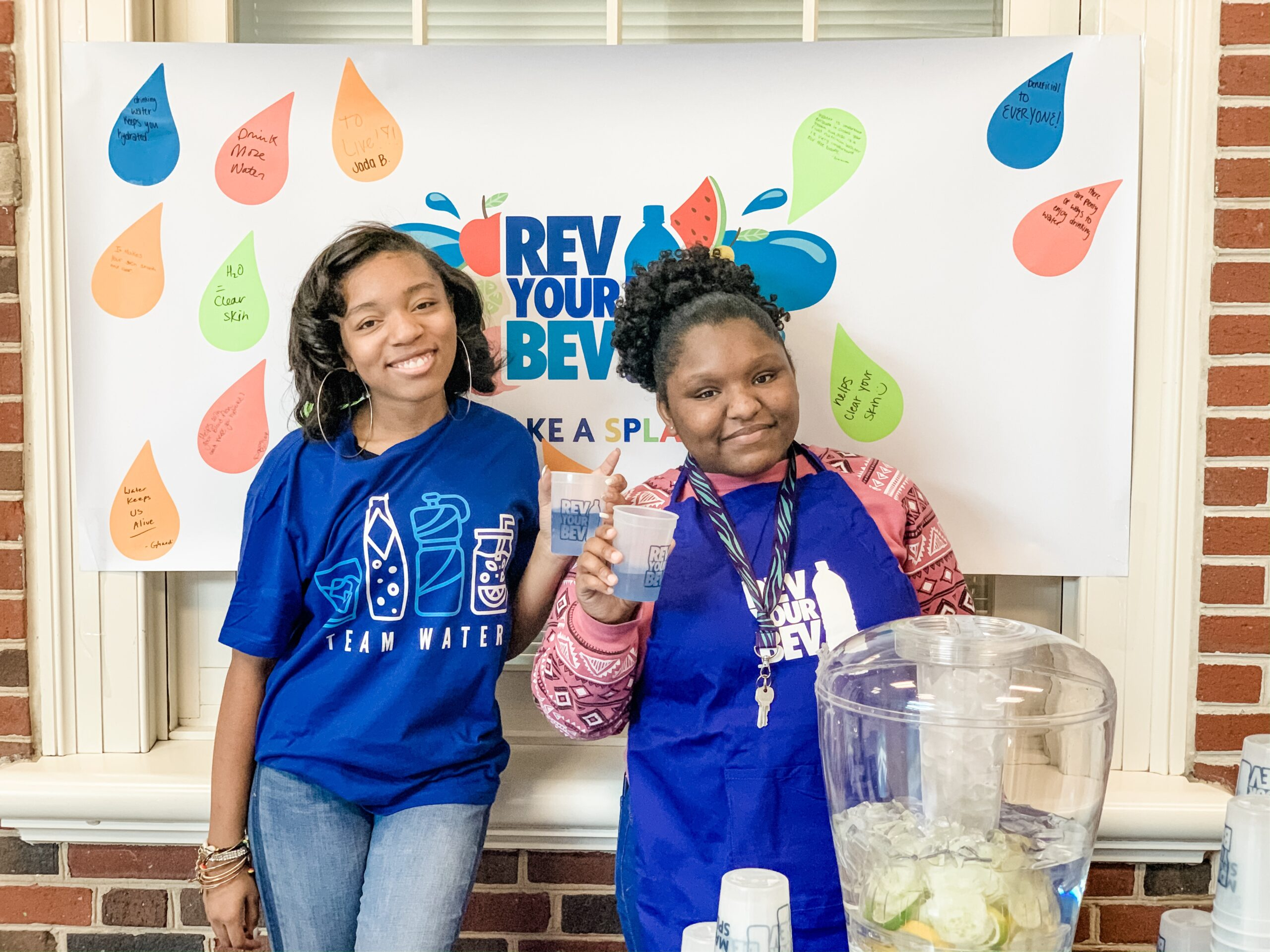 Two young high school students promoting Rev Your Bev